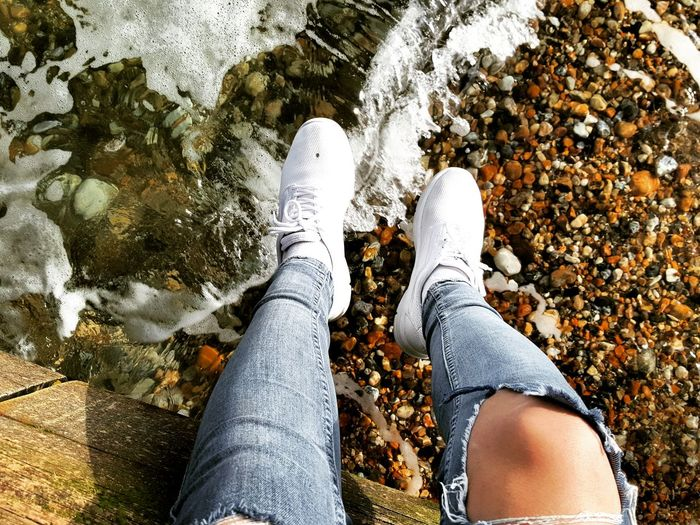 Low Section Of Person Dangling Legs Over Lake