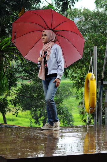 Protection Umbrella Rain One Person Real People Wet Water Security Leisure Activity Full Length Casual Clothing Tree Women Lifestyles Standing Monsoon Holding Day Rainy Season Outdoors