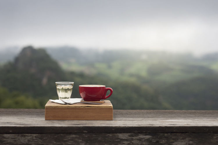 Coffee cup on table against mountain