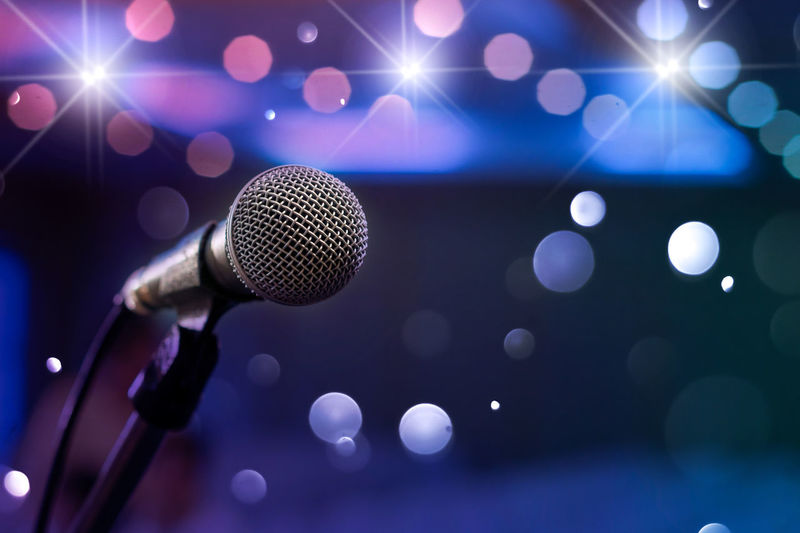 Close-Up Of Microphone In Stand Against Illuminated Lights