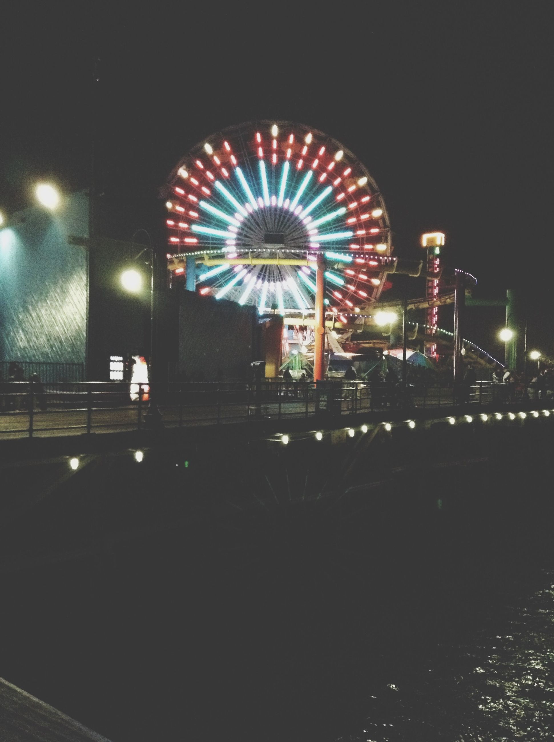 illuminated, night, arts culture and entertainment, built structure, architecture, amusement park ride, ferris wheel, amusement park, lighting equipment, building exterior, city, multi colored, low angle view, incidental people, sky, clear sky, outdoors, circle, travel destinations, decoration