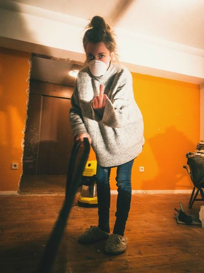 Portrait of woman showing obscene gestures while cleaning house