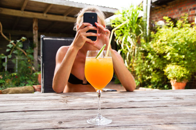 Woman Photographing Drink On Table