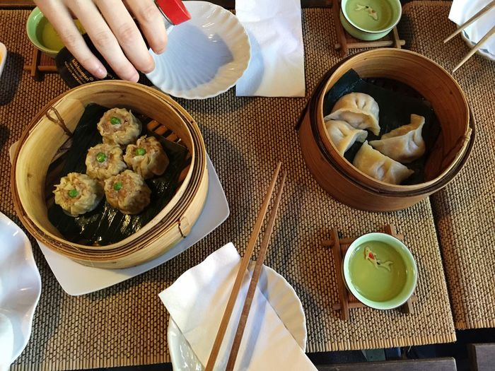Cropped image of person having chinese dumplings on table