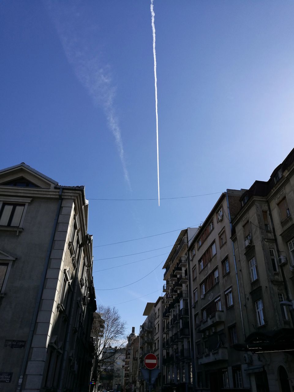 vapor trail, contrail, blue, built structure, low angle view, building exterior, no people, outdoors, architecture, clear sky, day, sky