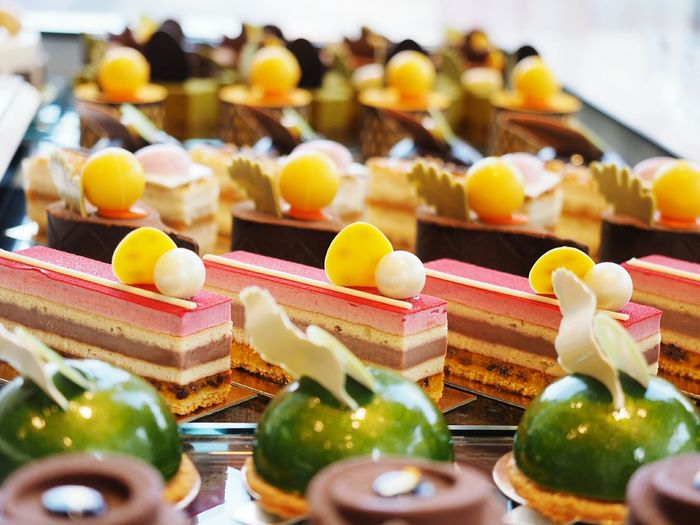 Close-up of garnished sweet cakes arranged in order