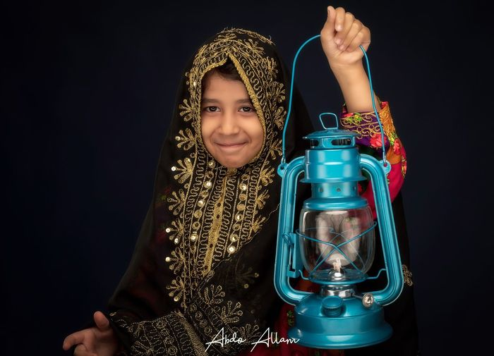 Qatari traditional dress for Ramadan Indoors  One Person Child Childhood Transparent Glass - Material Real People Females Lifestyles Women Front View Girls Studio Shot Portrait Pattern Container Holding Creativity Black Background