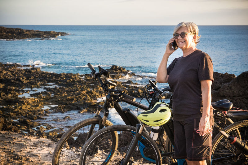 Senior woman talking through smart phone while standing by bicycle on beach