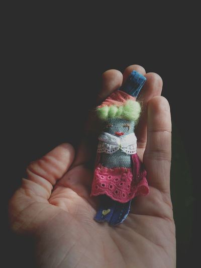 Cropped Image Of Person Holding Doll Against Black Background