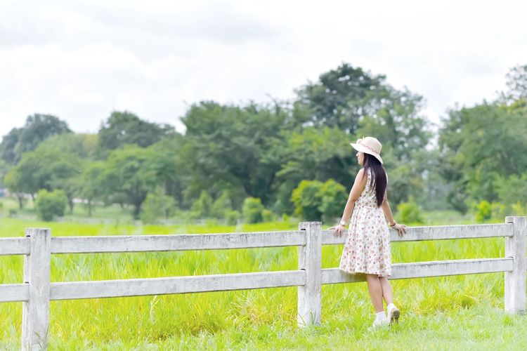 Woman Standing At Fence On Grassy Field Against Trees