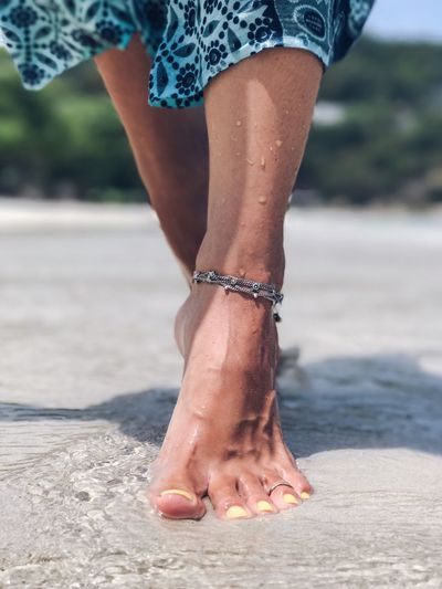 Low section of woman walking on shore at beach