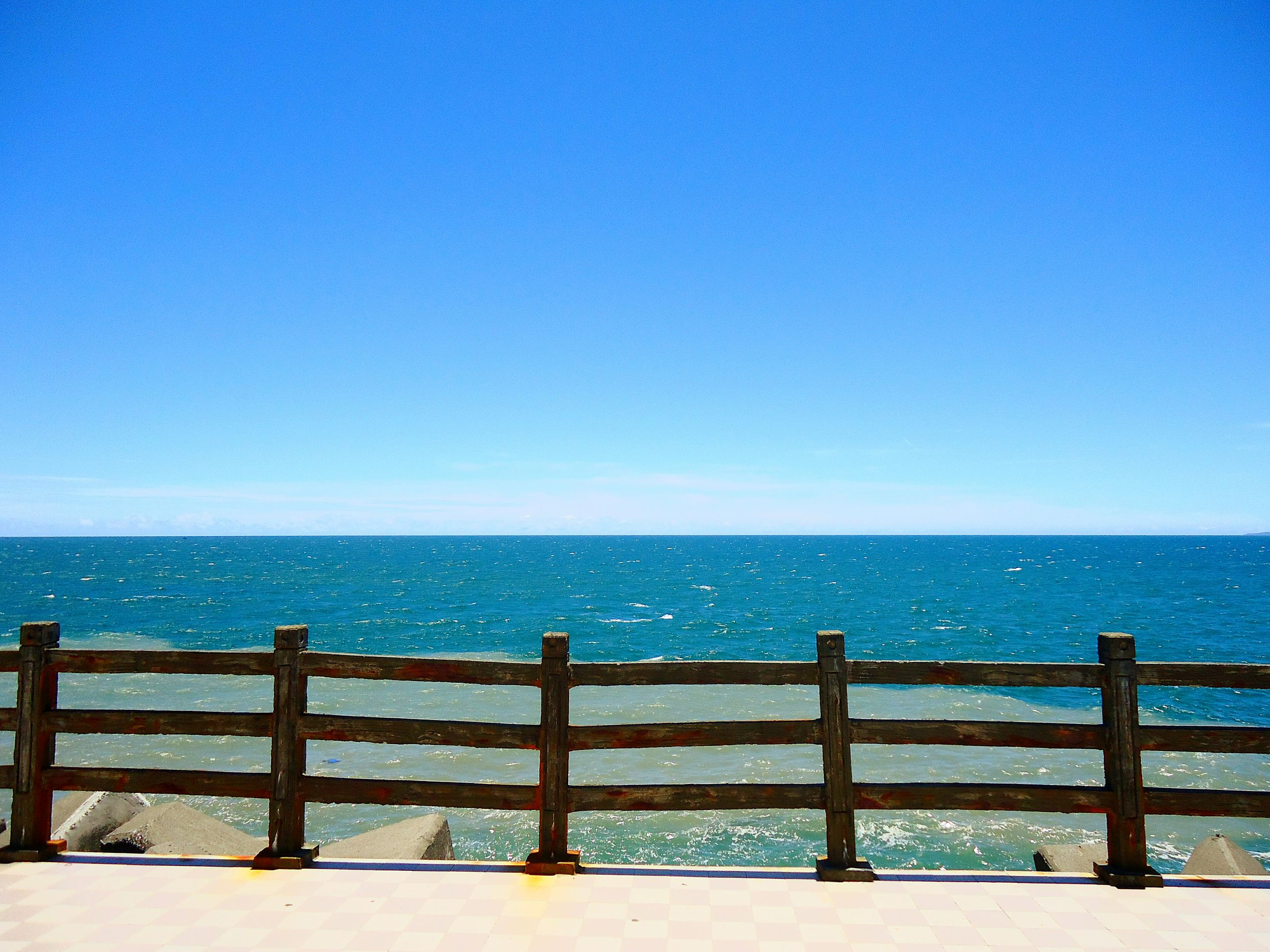 sea, horizon over water, water, blue, clear sky, tranquil scene, scenics, copy space, tranquility, beauty in nature, railing, beach, nature, idyllic, seascape, ocean, calm, outdoors, shore, remote