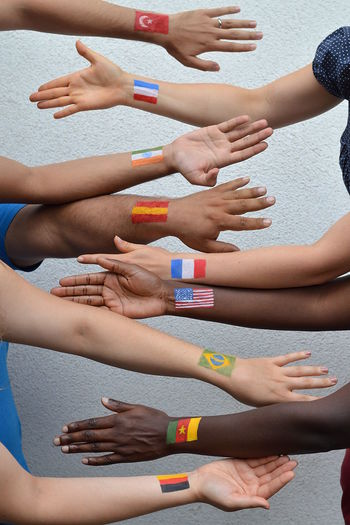 Cropped hands of people with flags on hand against wall