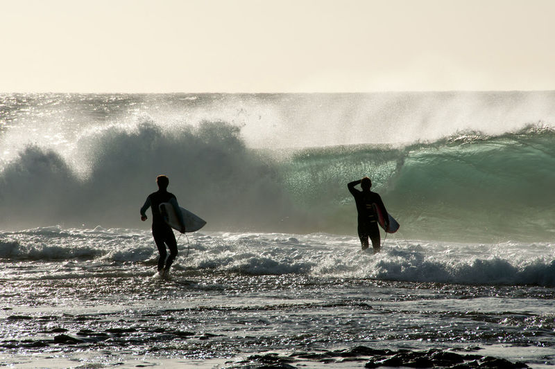 Men with surfboard standing by waves in sea