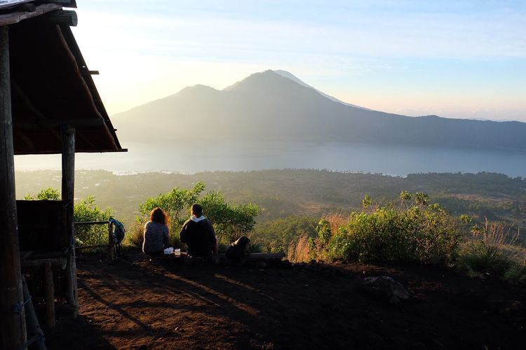 Rear View Of Man And Woman Sitting Against Mount Batur During Sunrise
