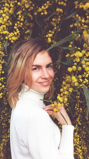 Close-Up Portrait Of Woman Smiling While Standing Amidst Yellow Flowers