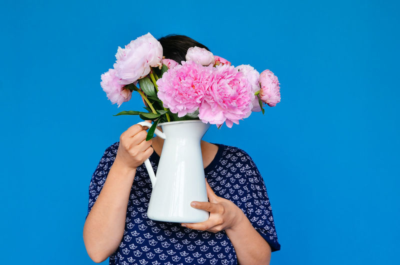 Woman Holding Pink Roses Vase In Front Of Face Against Blue Background