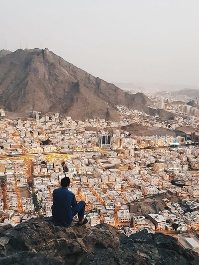 a man sitting on the edge of Jabal Al Nour (the mountain of light) where the holy Qur'an first came to the prophet Muhammad PBUH Islam Makkah EyeEm Selects KSA People Arab Mountain Politics And Government Sitting Spirituality Religion Place Of Worship Old Ruin Men Mountain Rear View Sky