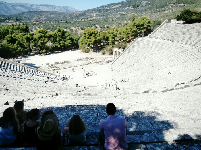 People at the great theatre of epidaurus in city on sunny day
