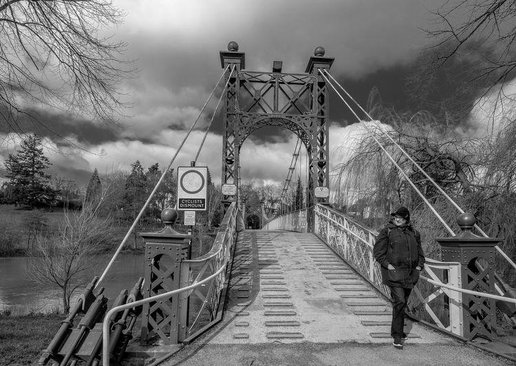 Man on bridge against sky
