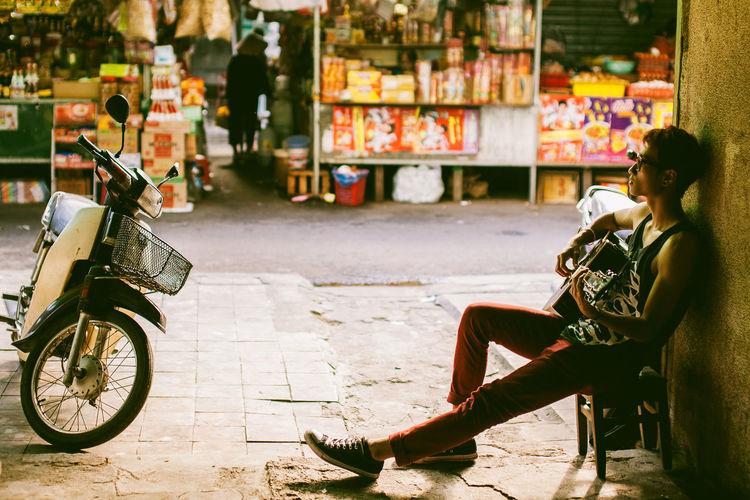 Man playing guitar while sitting on footpath at market