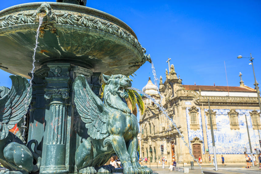 Close up of fountain of Lions, 19th century fountain in Parada Leitao Square in historic city of Porto in Portugal. The beautiful Carmo church on blurred background. Portugal Porto Tourism City Aerial View Cloudscape Cityscape Landscape Panorama Europe People Church Church Architecture Architecture Town Porto Portugal 🇵🇹 Monment Oporto City Oporto Downtown Oporto Streets Sculpture Representation Statue Art And Craft Human Representation Travel Destinations Built Structure Building Exterior History The Past Travel Low Angle View Male Likeness Nature Creativity No People Outdoors Architectural Column