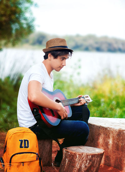 Sitting One Person Young Adult Casual Clothing Focus On Foreground Young Men Three Quarter Length Real People Lifestyles Leisure Activity Day Hat Side View Lake Holding Cap Clothing Nature Outdoors School Bag Grass Music Travel