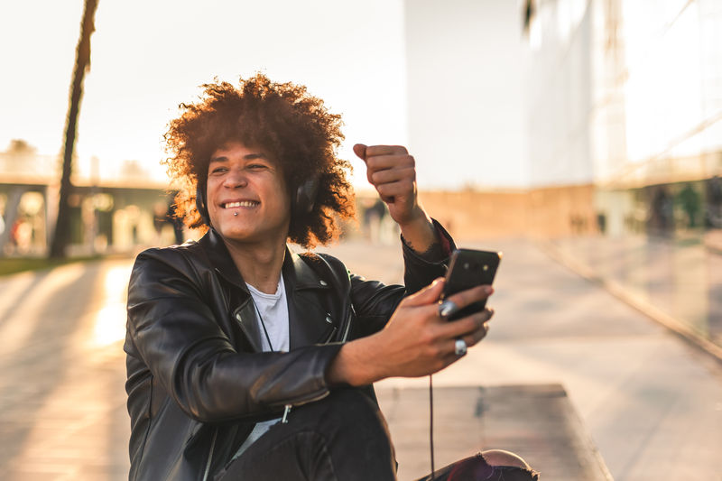 Young man using mobile phone in city