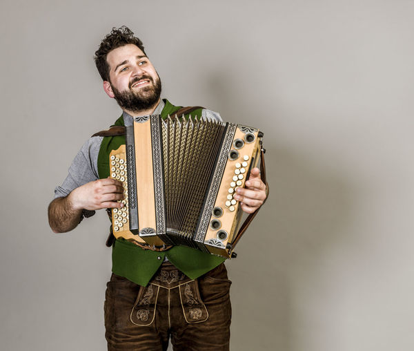 Musician Costume Leather Trousers Tradition Traditional Austria Green Pose Accordion Man Young Shorts Friendly Proud Happy Play Music Fun Joy Single One Background Copy Space Studio Entertainment Mountains Shirt STAND Hobby Leisure Cool Studio Shot One Person Indoors  Young Adult Casual Clothing Gray Background Standing Gray Musical Instrument Front View Holding Young Men Three Quarter Length Arts Culture And Entertainment Playing Portrait