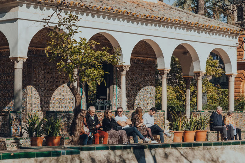 People sitting by plants against building