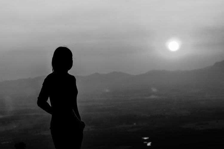 Silhouette woman standing against mountain and sky during sunset