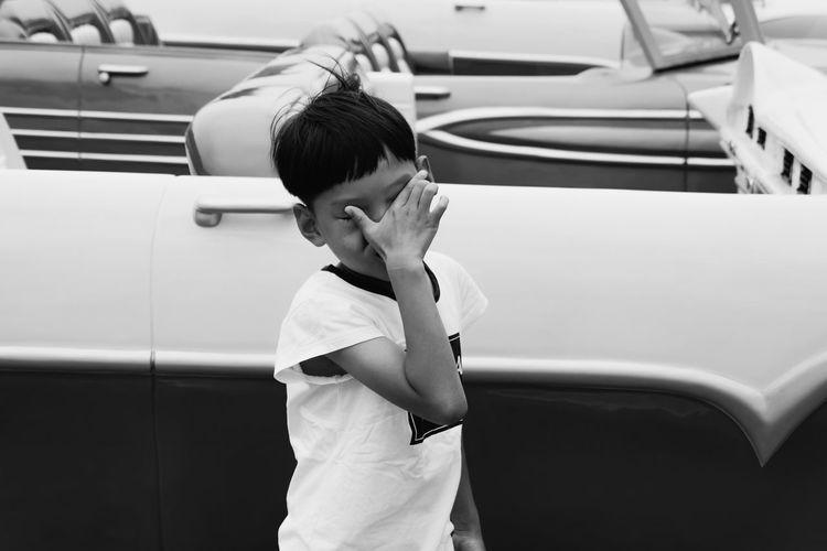 Boy standing against car