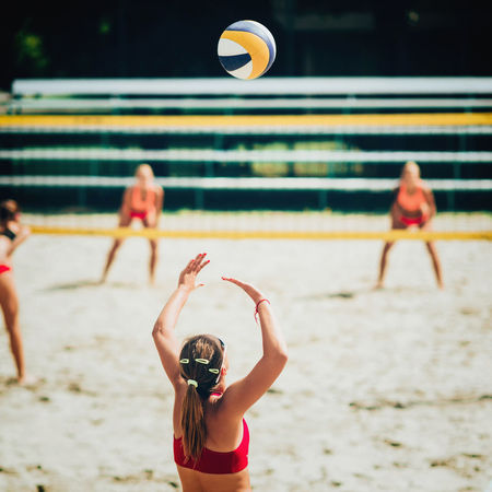 Female Team Playing Beach Volleyball, Focus On Serving Player And The Ball Beach Volleyball Caucasian Girls Court Court Activity Arms Raised Ball Beach Bikini Day Match Net - Sports Equipment Outdoors Playing Sand Sport Sunny Day Team Team Sport Volleyball Women Women Only Young Woman