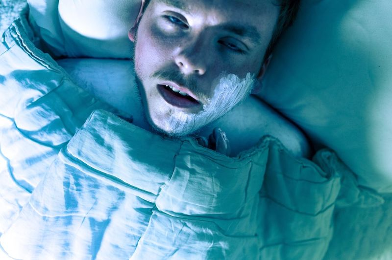 Sick Man With Cream On Face Lying Down In Bed