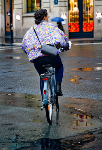 Rear view of woman riding bicycle on wet street