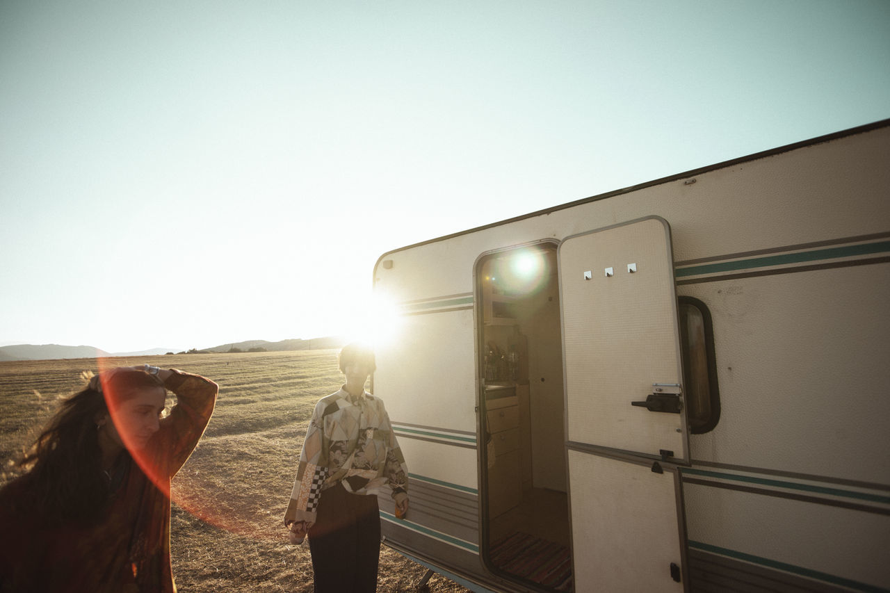 Friends standing by camper van on field during sunny day
