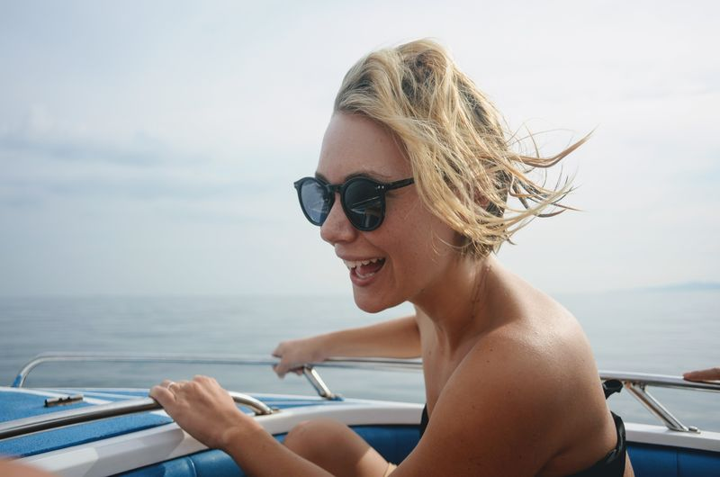 Beautiful Woman Blond Hair Boat Day Focus On Foreground Headshot Horizon Over Water Leisure Activity Lifestyles Mode Of Transport Nature Nautical Vessel One Person Outdoors Real People Sailing Sea Sky Smiling Sunglasses Transportation Travel Vacations Water Young Adult