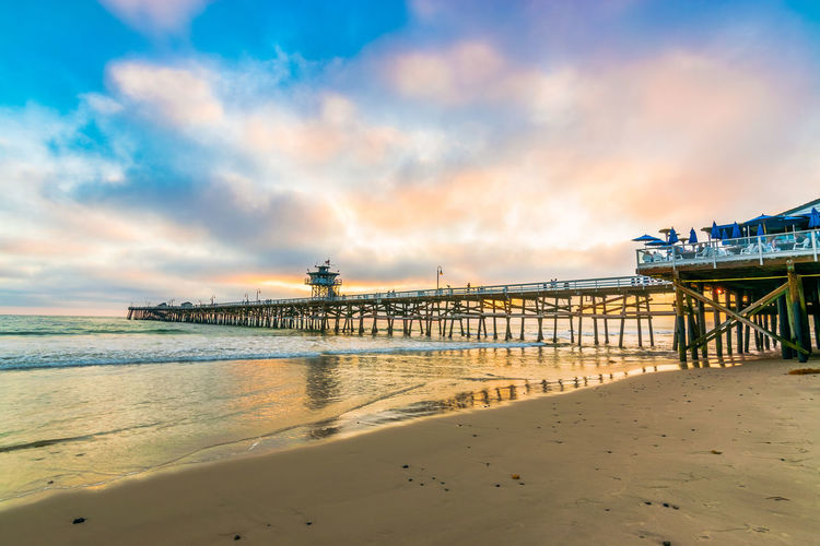 View of pier on beach against cloudy sky