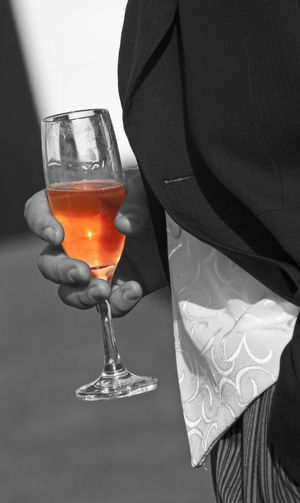Selective colour concentrates the eye on the glass and contents - smart outfit and a symbol of socialising and relaxation Cambridge Glass Monochrome Morning Suit Pink Champagne Selective Colour Summer Sunshine Wedding Wine Not