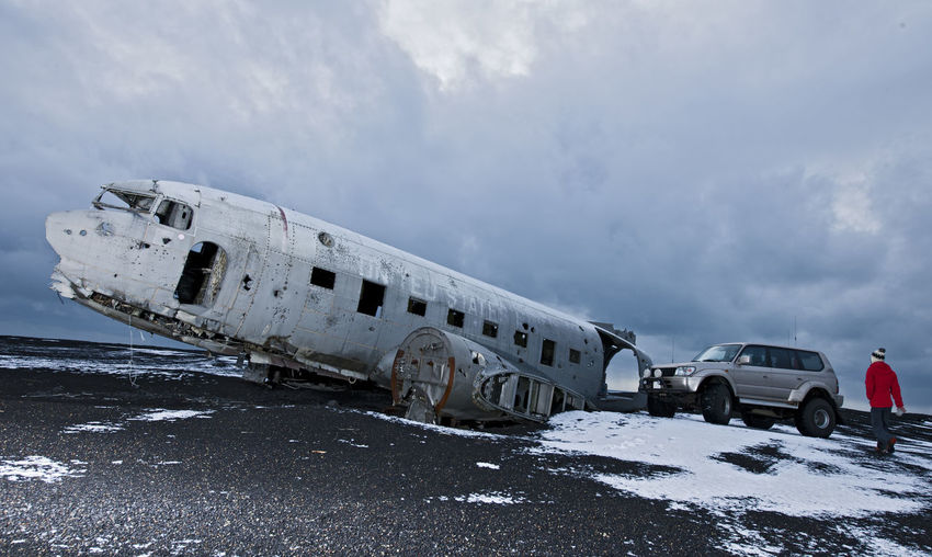 Abandoned airplane on snow covered land against sky
