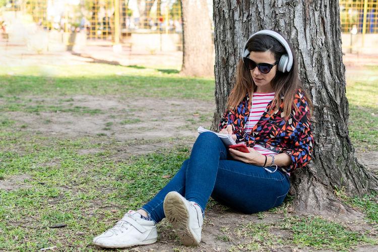 Woman wearing sunglasses sitting on tree trunk