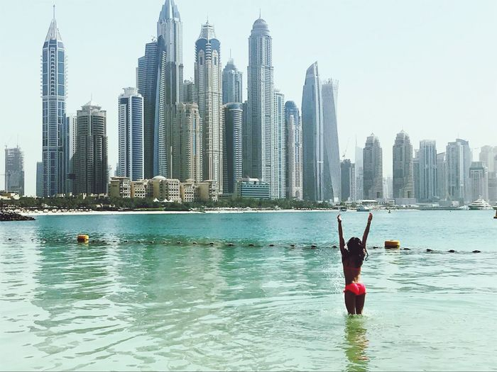 Young woman enjoying in sea against buildings
