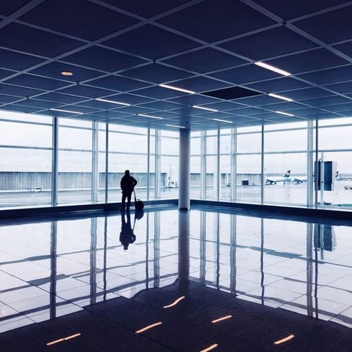 Silhouette man standing by window in airport lobby