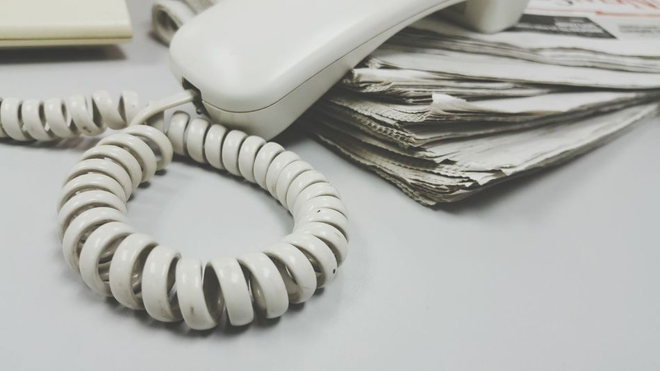Telephone and newspaper Connection Cable Phone Cord No People Close-up Indoors  Day Communication Telephone Newspaper