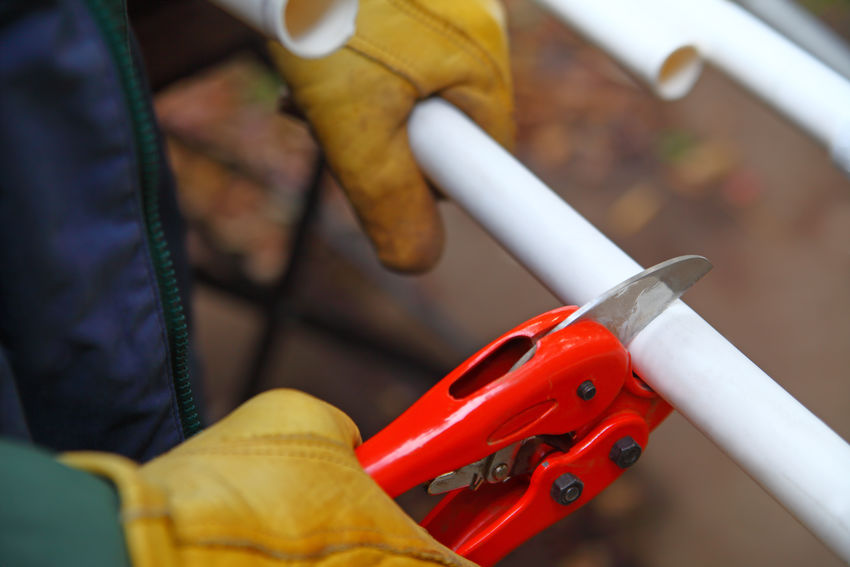 Handyman cuts PVC piping Close-up Construction Cutter Cutting Pvc Pipe Day Handyman Man Natural Light One Person Outdoors Piping POV Red Textures Using Tool Wearing Gloves White Work Gloves Yard Maintenance