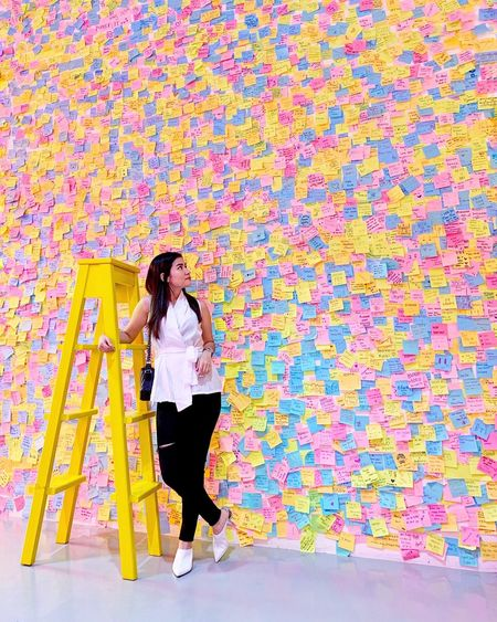 Full length of woman standing against multi colored adhesive notes on wall