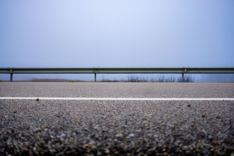 Surface level of road against clear sky