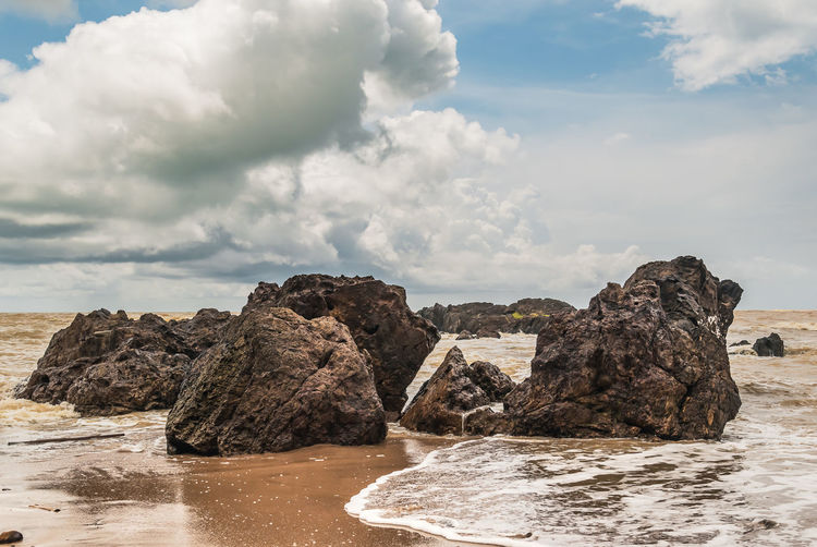 Rock formations on shore against sky