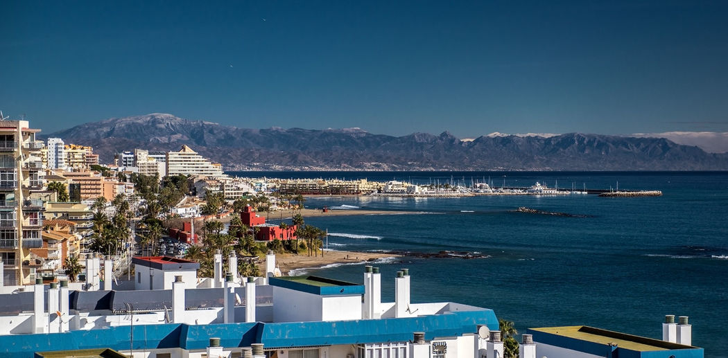 Scenic view of buildings by sea against mountains at costa del sol