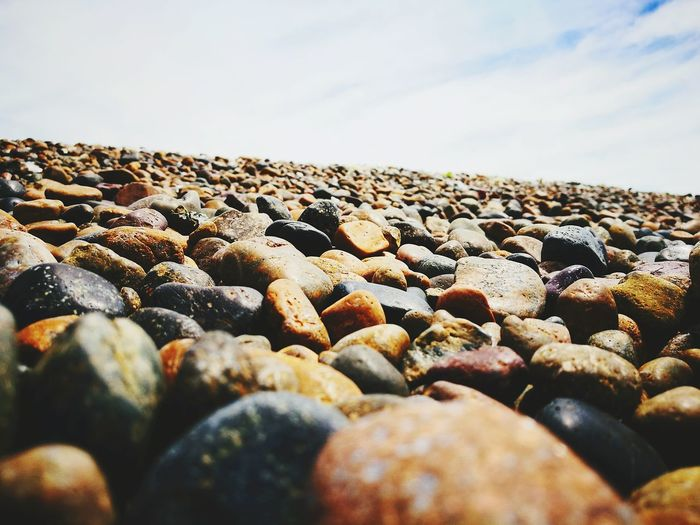 Close-up of pebbles on beach against clear sky